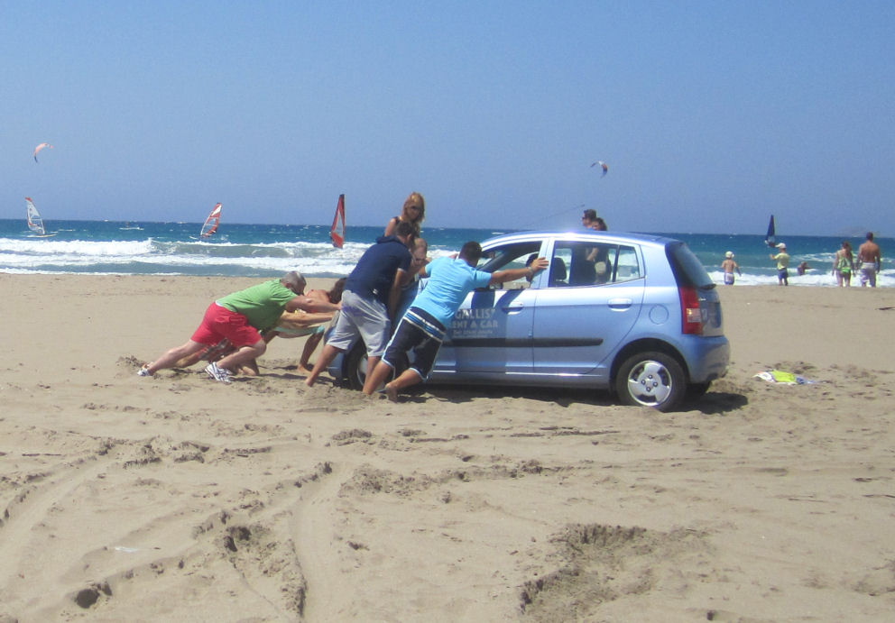 People trying to push a car stuck in the sand on Prasonissi Beach. Click for Travel Insurance