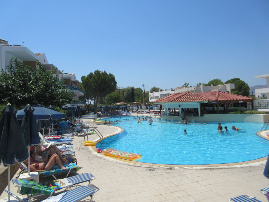 Pefki Islands hotel pool area with peopl swimming and sunbathing around the edge. Click Here to go the package holidays page.
